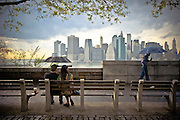 A couple, taking shelter under an umbrella, are seating on a bench and enjoying the Wall Street skyline from Brooklyn Heights, New York, 2011.