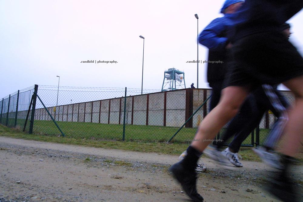 Während Aktivisten der Umweltorganisation Robin Wood den Schachturm 2 des Erkundungsbergwerkes in Gorleben besetzt und ein Transparent errollt haben (Hintergrund), laufen Polizisten bei ihrem Frühsport am Zaun des Geländes entlang. In der Zeit der Grosseinsätze wegen der Castortransporte sind im Gelände des möglichen Endlagers Einsatzkräfte untergebracht.