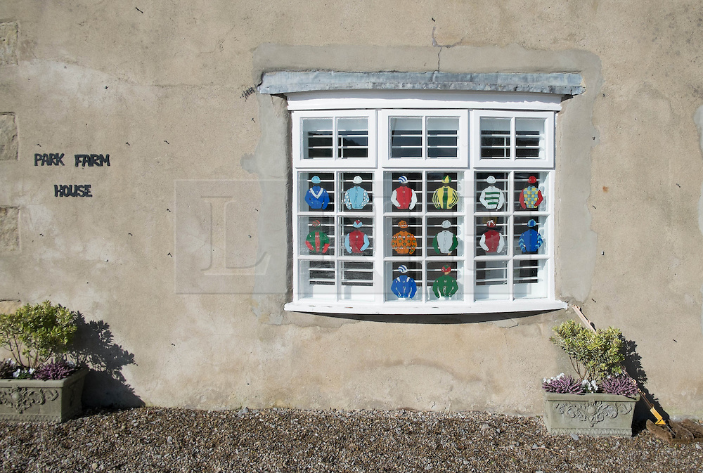 © Licensed to London News Pictures. 22/03/2014<br /> <br /> Middleham, North Yorkshire<br /> <br /> Racing colours are displayed on a window at the Mark Johnston stables in Middleham, North Yorkshire. Race horses have been trained in Middleham for over 200 years using the extensive gallops on the high moor. There are currently 15 stables based around the small Yorkshire village.<br /> <br /> Photo credit : Ian Forsyth/LNP