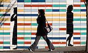 Woman talking on cellphone walks past wall of shadow figures on Pike Street, Seattle, Washington