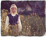 Young Estonian girl in traditional costume outside summer cottage