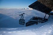 Luftseilbahn auf dem Gipfel des Moléson (2002 m ü. M.) im Winter, mit Blick auf die sonnigen Berggipfel der Freiburger Voralpen. Arrivé du télécabine au sommet du Moléson sur fond des préalpes fribourgeoises  hivernales ensoleillés