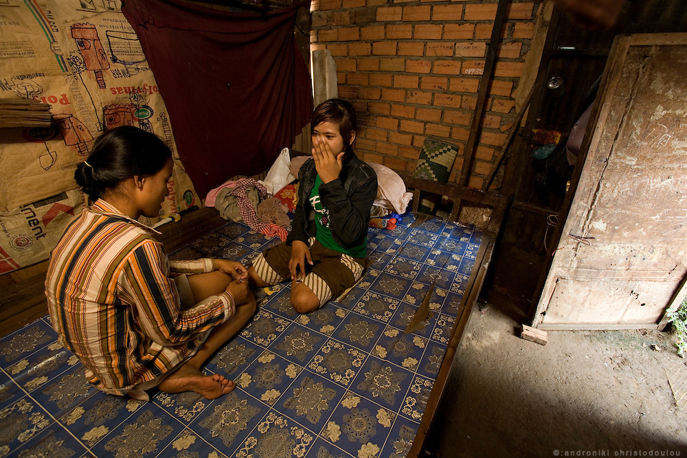 """Son Rathany (14) (R) and Rous Mach (15) (L) who are both working as prostitutes, in the room where they sleep and sometimes bring clients, in a slam behind the """"building"""" in Phnom Penh. They both started working as prostitutes about half a year ago. Son after her family broke up and Rous after being tricked to start going to bars by a divorced female friend of hers. They take 1-2 clients a night. Rous goes mainly to """"Martini Pub"""" a bar where foreign men go to pick up prostitutes. Son looks very young so it is more difficult for her to go in the bars but she refused to say how she finds customers."""
