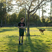 ROYAL PALM BEACH, FLORIDA, MARCH 15, 2017<br /> Tyler Greaux, 14, watches his family's recently adopted dog &quot;Ginger&quot; run around in the dog park a short walk from their house. Their mother Cynthia Greaux is able to use vouchers to pay for their enrollment at a private school that specializes in educating children with dyslexia.<br /> (Photo by Angel Valentin/Freelance)