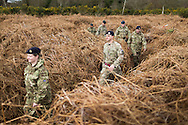 Soldiers explore an overgrown trench in a practice battlefield, where thousands of troops trained before embarking for the battlefields of Europe during World War One. The trench system was been discovered by chance on the Browndown Ministry of Defence site in Gosport, Hampshire, England. March 6, 2014. AFP PHOTO / CHRIS ISON.