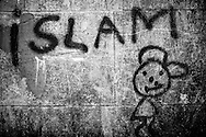 """Islam"" graffiti with a happyt face on the asylum center's wall left by one of its residents. The walls of the center are like an improvised journal of the past and present residents. FEDASIL Rixensart asylum center. Rixensart, Belgium. April 2015. I took these photographs during an international volunteer program that I liderate with an international volunteering group."
