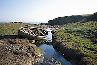 Abandoned boat by stream in peat