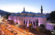 Grand Mosque or Ulu Cami seen at dusk behind a busy road, built 1396-99 under the Ottoman Sultan Bayezid I by the architect Ali Neccar in the Seljuk style, Bursa, Turkey. It is a large rectangular building with 2 minarets, and 20 domes supported by 12 columns. Supposedly the 20 domes were built instead of the 20 separate mosques which Sultan Bayezid I had promised for winning the Battle of Nicopolis in 1396. The mosque is in the old city centre of Bursa and remains the largest mosque in the city. Picture by Manuel Cohen