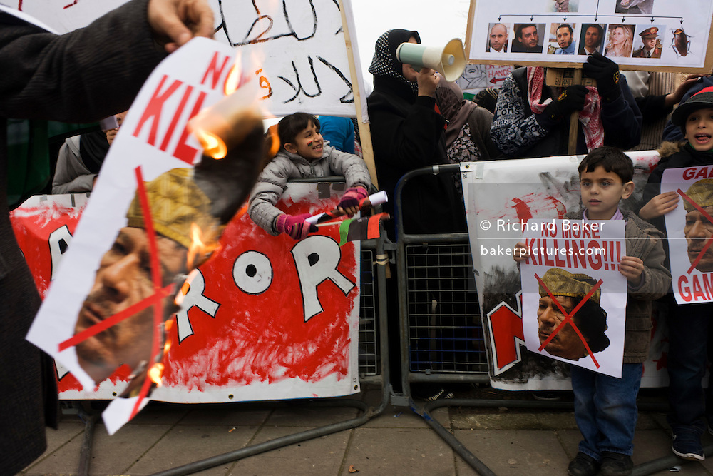 Exiled Libyan children participate in the demand for the death dictator Colonel Gaddafi during protests opposite their London embassy during the uprising. A man walks past with a print of Gaddafi's face, flames licking around his head and the children - two young boys - watch as they hold their own posters that read No More Killing - calling for an end to the leader's atrocities against his own people.