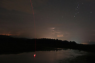 Mamakating, New York -  Lightning from distant thunderstorms lights up clouds above the Bashakill Wildlife Management Area as stars shine higher in the night sky on July 17, 2010. The red line and light in the water is from a fisherman casting a glowing bobber into the water.