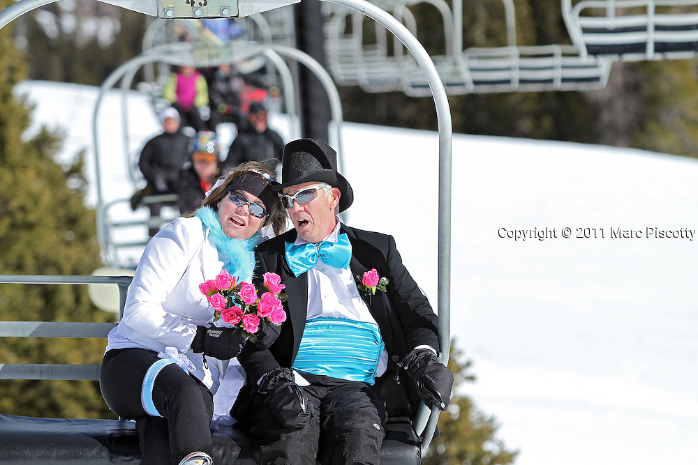 LOVELAND SKI AREA, CO - FEBRUARY 14: Michael and Marcia Linley of Fort Collins, Co. sing wedding tunes as they ride Chair 2 to the top of Loveland Ski Area in Colorado prior to the start of the 20th Annual Marry Me & Ski Free Mountaintop Matrimony on Valentine's Day Monday, February 14th. The mass wedding ceremony was held at noon at 12,050 feet outside of the Ptarmigan Roost Cabin at Loveland. More than 75 couples were pre-registered to get married or renew their vows high on The Continental Divide in this yearly Loveland tradition.  Following the ceremony couples were invited to a casual reception complete with a champagne toast, wedding cake and music. The Linleys are avid skiiers and were renewing their vows after 34 years of marriage. (Photo by Marc Piscotty © 2011)