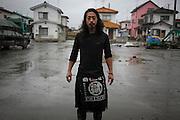 Chun Kawara vit au cantre de réfugiés Minato Shôgakkô..Avant le passage du tsunami, il était artiste international. Il définissait sa pratique comme du street art. Son tracé et son style en figuration libre offrait un juste compromis en rigueur plastique et folie festive. Il investissait les volumes en peignant sols et plafonds des musées ou dautres espaces publics lors expositions en Corée, en Thaïlande et en Chine..Cette vie sécrit aujourdhui au passé car Chun Kawara ne désire plus peindre ni exposer depuis que ce jour tragique lui a enlevé sa femme..Depuis le 11 mars, Chun Kawara est volontaire à la reconstruction et au nettoyage dans le quartier du port. Il encadre les volontaires, restaure des vélos pour la communauté, ou dessine pour les enfants du centre des images aux  messages joyeux Aussi, sa gaieté quotidienne et sa disponibilité aident la communauté à voir leur renouveau sous un meilleur jour. Toutefois, il porte sur sa tenue de travail le mot Gokku (prison), seul signe extérieur dune condition intérieure quil combat..À Ishinomaki, tout le monde porte la tristesse en soi. Chacun la dissimule ou la manipule pour lextérioriser autrement. Les pleurs visibles ont peu de place, lheure est au retour à la vie et aux initiatives actives.