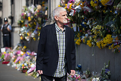 © Licensed to London News Pictures . 27/03/2017 . London , UK . The Metropolitan Police's longest serving officer , MICK MOUNTAIN (now retired) surveys flowers and tributes fixed to railings outside Parliament in Westminster . Tributes have been left in response to Khalid Masood's terrorist attack and the killing of PC Keith Palmer . Photo credit: Joel Goodman/LNP