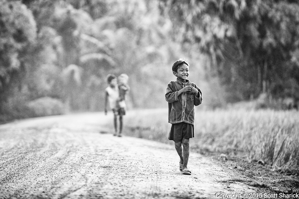 A young Cambodian boy makes his way down a dirt road in rural Cambodia to greet the foreigner with a camera.