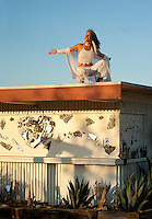 Smiling welcoming woman on the roof of a simple dwelling with a mirror heart on it's exterior wall.  And, if you look closely, the shadow of a tall gateway can also be seen cast upon the wall.