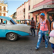 Cubans manage their daily life wether waiting for overcrowded busses or doubling up on old classic cars and motorcycles. Walking is standard mode of transportation. <br /> Photography by Jose More
