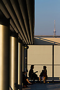 Women talk on the roof of the new Ginza 6 shopping Mall with Tokyo Skytree in the background . Ginza, Tokyo, Japan. Friday October 27th 2017