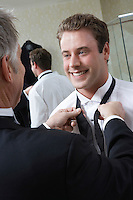 Man tying groom's bow tie