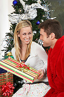 Couple with present by Christmas tree