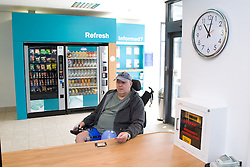 Male wheelchair user checking in at the reception desk at his local sports leisure centre,