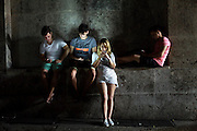 Cuban youth hop on a hotel wifi signal on a dark street in Havana, Cuba no June 14, 2015.  In one of the last countries where most people are offline, Cuban youth are bursting with a desire to connect to the world.