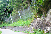Thick steel  fences are used to stop avalanches from reaching the road. Photographed in Tyrol Austria