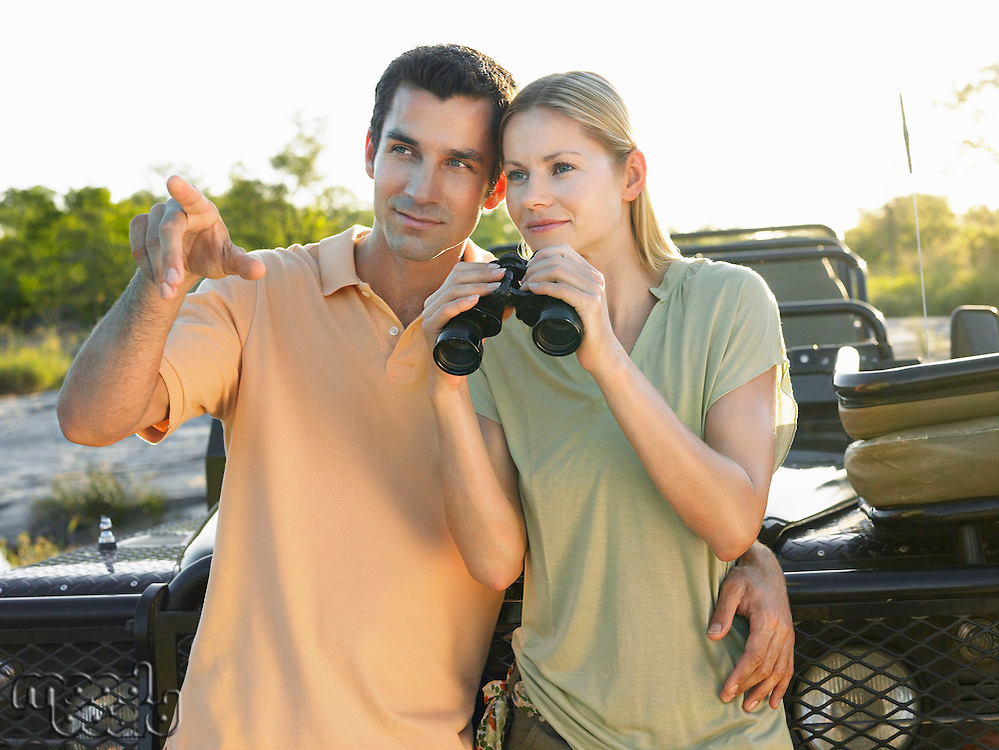 Young couple standing by jeep man pointing woman holding binoculars