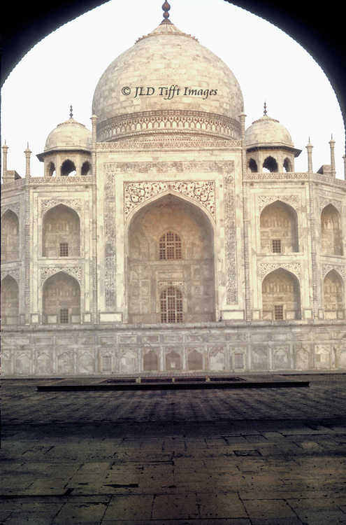 Taj Mahal from the east at sunrise: seen through the arched entrance of the guest house which frames the east side of the tomb..