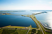 Nederland, Zeeland, Grevelingen, 12-06-2009; Grevelingendam naar Bruinisse op Duiveland (aan de horizon), naar links de Philipsdam naar St. Philipsland met de Krammersluizen. De sluizen maken scheepvaartverkeer naar de Oosterschelde (aan de verre horizon) mogelijk. Rechts de Grevelingen of Grevelingenmeer, het grootste zoutwatermeer van Europa, ontstaan door het afsluiten van de zeearm door de Brouwersdam in het kader van de Deltatwerken  (1971). Door het verdwijnen van het getij is de ecologische kwaliteit van het water steeds verder achteruitgegaan, er zijn initiatieven om een opening in de Brouwersdam te maken om zo het getij deels terug te laten keren..Swart collectie, luchtfoto (25 procent toeslag); Swart Collection, aerial photo (additional fee required).foto Siebe Swart / photo Siebe Swart