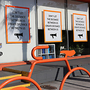 A storefront with encouraging social distancing signs is seen during the Coronavirus (COVID-19) non-essential business closures on Saturday, March 28, 2020 in Orlando, Florida. Orange County government ordered all non-essential businesses such as barber shops, nail salons, gyms and massage parlors to shut down. (Alex Menendez via AP)