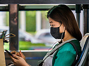 31 JANUARY 2019 - BANGKOK, THAILAND:   A woman wearing a breathing mask on a Bangkok bus. The Thai government has closed more than 400 schools for the rest of the week because of high levels of pollution in Bangkok. At one point Wednesday, Bangkok had the third highest level of air pollution in the world, only Delhi, India and Lahore, Pakistan were worst. The Thai government has suspended some government construction projects and ordered other projects to take dust abatement measures. Bangkok authorities have also sprayed water into the air in especially polluted intersections to control dust. Bangkok's AQI (Air Quality Index) Thursday morning was 180, which is considered unhealthy for all people.      PHOTO BY JACK KURTZ