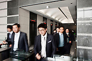 Employees at the Hyundai Motor Group headquarters leaving for lunch. Lunchbreak for everyone in the building is between 12 and 1pm. Seoul, Korea. 2012
