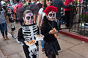 Young girl dressed in costumes walk through the cemetery during Day of the Dead festival November 2, 2017 in Quiroga, Michoacan, Mexico.  The festival has been celebrated since the Aztec empire celebrates ancestors and deceased loved ones.