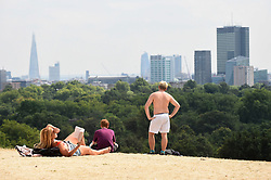© Licensed to London News Pictures. 25/07/2018. LONDON, UK.  People enjoy the weather atop Primrose Hill amidst parched grass and hot conditions.  The forecast is for temperatures to rise to 35C by the end of the week.  Photo credit: Stephen Chung/LNP