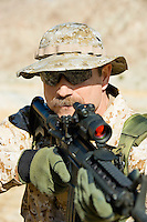 Soldier aiming rifle outdoors (close-up)