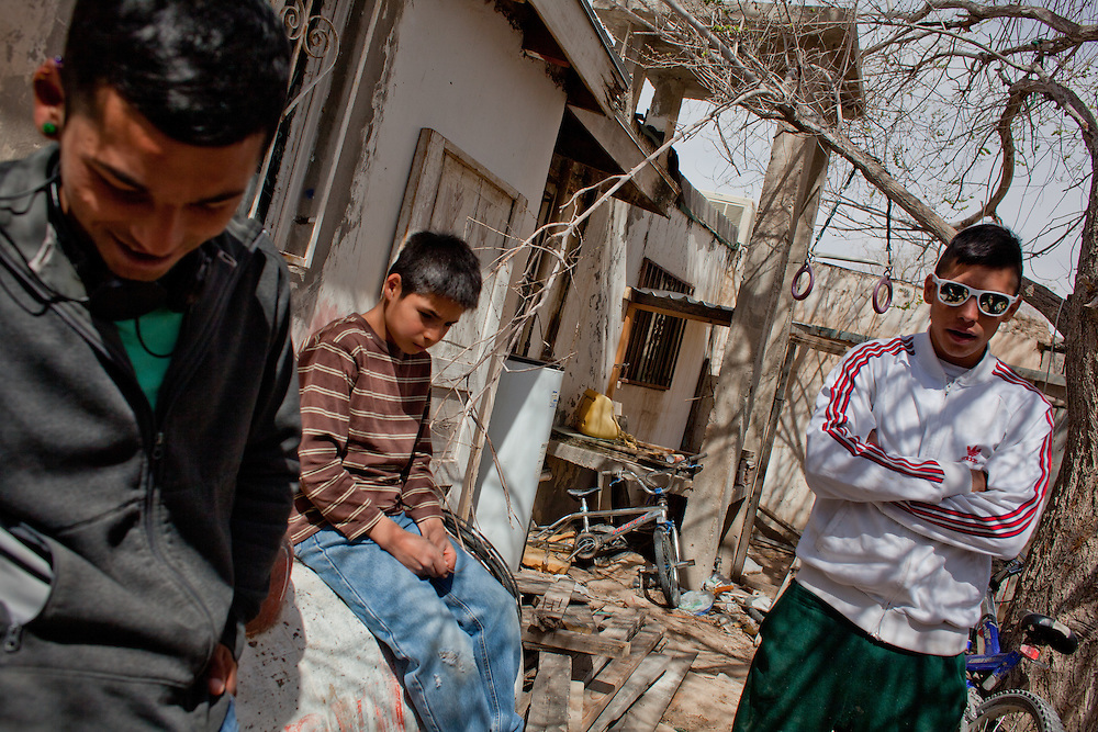 Manny hangs out with his brothers outside his house. Recently their friend Chino was murdered at the inaguration of a new soccer field that was built between three neighborhoods that have a history of violence. The boy in the center of the photograph saw the murder.