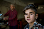 Radwan's son Mohammed helps his father at his tea shop, which he recently reopened in the old city of Mosul.<br />