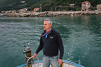 """PISCIOTTA, ITALY - 21 APRIL 2018: Fisherman Vittorio Rimbaldo (56) drives his fishing boat to go out fishing alici di Menaica (Menaica anchovies) in Pisciotta, Italy, on April 21st 2018.<br /> <br /> Former restaurant owners Donatella Marino and her husband Vittorio Rimbaldo have spent the recent years preparing and selling salted anchovies, called alici di menaica, to a growing market thanks to a boost in visibility from the non-profit Slow Food.  The ancient Menaica technique is named after the nets they use brought by the Greeks wherever they settled in the Mediterranean. Their process epitomizes the concept of slow food, and involves a nightly excursion with the special, loose nets that are built to catch only the larger swimmers. The fresh, red anchovies are immediately cleaned and brined seaside, then placed in terracotta pots in between layers of salt, to rest for three months before they're aged to perfection.While modern law requires them to use PVC containers for preserving, the government recently granted them permission to use up to 10 chestnut wood barrels for salting in the traditional manner. The barrels are """"washed"""" in the sea for 2-3 days before they're packed with anchovies and sea salt and set aside to cure for 90 days. The alici are then sold in round terracotta containers, evoking the traditional vessels that families once used to preserve their personal supply.<br /> <br /> Unlike conventional nets with holes of about one centimeter, the menaica, with holes of about one and half centimeters, lets smaller anchovies easily swim through. The point may be to concentrate on bigger specimens, but the net also prevents overfishing."""