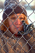 Homeless woman age 50 peering through chain link fence. St Paul Minnesota USA