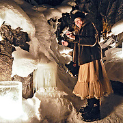 Moira Sauer adds to the candles and ice lanterns lighting up a frozen waterfall near McLean Lake in Whitehorse, Yukon to celebrate the winter solstice.