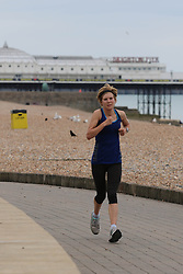 © Licensed to London News Pictures. 15/06/2014. Brighton, Uk. Dozens of runners exercise on Brighton Promenade. Despite a slow and cloudy start to the weekend on Saturday today, Sunday 15/06/2014 looks set to be a nice and warm day with temperatures up to 20C. Photo credit : Hugo Michiels/LNP