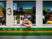 11 APRIL 2015 - BANGKOK, THAILAND:  A woman looks out the window of a 3rd class train car at Hua Lamphong train station in Bangkok. More than 130,000 passengers streamed through Bangkok's main train station Friday ahead of Songkran, Thailand's traditional new year celebration. Songkran will be celebrated April 13-15 but people started streaming out of Bangkok on April 10 to go back to their home provinces.   PHOTO BY JACK KURTZ