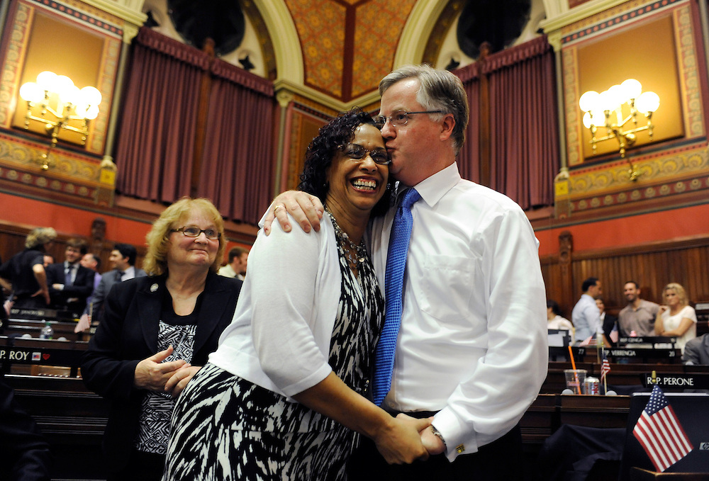 House Majority Leader Brendan Sharkey, D-Hamden, right, kisses Toni Walker D-New Haven as Peggy Sayers, D-Windsor, left, looks on at the close of the legislative session at the Capitol in Hartford, Conn., early Thursday, June 9, 2011. (AP Photo/Jessica Hill)