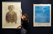 © Licensed to London News Pictures. 25/11/2011, London, UK. A Bonhams worker hangs one of David Hockney's Soft Celia prints valued at 15,000 - 20,000 GBP. They are an edition run of 35. Preview of Bonhams print sale today 25 November 2011. 'Single dollar' works by Andy Warhol feature in Bonhams' print sale which is being hung for viewing. The signed prints, estimated at between £15,000- 20,000, represent the link Warhol often made between art and money, underlined by the high prices paid for them by collectors at the time and ever since. Photo credit : Stephen Simpson/LNP