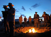 Cowboys and cattle drive guests huddle around the campfire eating cobbler during the annual Reno Rodeo cattle drive which brings the livestock for use in the rodeo into town.