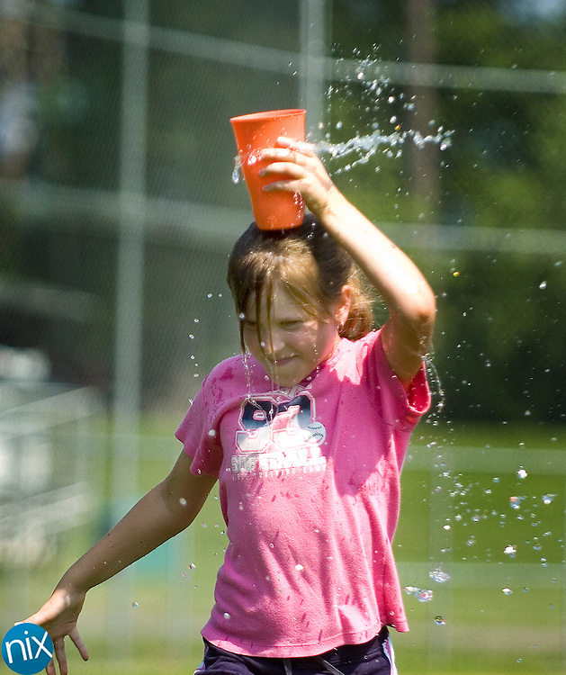 Carin Harmon, a fourth-grader in Stacy Hulen's class at Winecoff Elementary School, tries to keep as much water in a cup as he can while running back to his team during a game at the school's field day activities Tuesday Afternoon.
