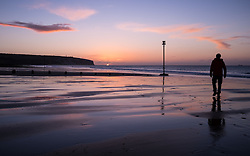 © Licensed to London News Pictures. 07/04/2016. Sandown, UK. A man watching the sunrise at Sandown Bay on the Isle of Wight this morning, Thursday 7th April 2016. Photo credit : Rob Arnold/LNP