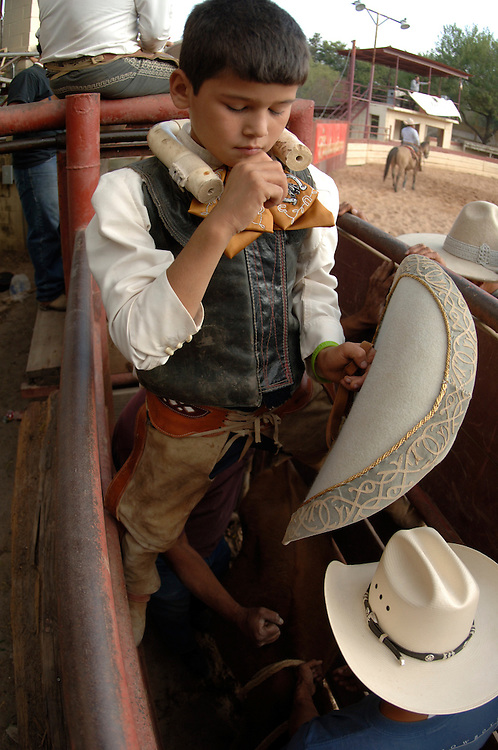 SAN ANTONIO, Texas -- Mark Velasquez (10) prepares for and competes at a San Antonio Charro Association hosted Charreada on Oct 23th, 2005 at the San Antonio Charro Ranch, 6126 Padre Dr. Shortly before a bull ride he used a cellular phone to chat with his mother Jovon Velasquez  who was in the arena seating area. (Photo by Lance Cheung)
