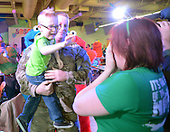 LANGHORNE, PA -  MARCH 15:  Tec Sgt. Justin Bright hugs his wife Tiffany Bright and his son Gerrin Bright (C), 4, after returning from Iraq at Sesame Place March 15, 2014 in Langhorne, Pennsylvania.  (Photo by William Thomas Cain/Cain Images)