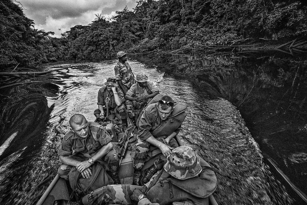 French guiana, St Georges, frontiere franco-bresilienne.<br /> <br /> Mission de reconnaissance sur la Gabaret, affluent de l'Oyapock, pour les legionnaires du 3e REI. Separee du Bresil par le fleuve Oyapock, St Georges est un des gros points de passage de l'immigration clandestine entre les 2 pays. Les garimpeiros bresiliens arrivent d'Oiapoque sur la rive bresilienne pour tenter leur chance sur les chantiers d'orpaillage legaux ou clandestins guyanais.<br /> La construction d'un pont devrait prochainement permettre le passage du fleuve. <br /> L'etat fran&ccedil;ais entend maintenant controler cette frontiere jusqu'ici permeable. La legion intervient dans des missions de renseignement pour loger les differents sites que les gendarmes tentent de demanteler. Depuis 2004, l'offensive gouvernementale se durcit. Deux escadrons de gendarmerie mobile sont affectes en permanence a la lutte contre l'orpaillage clandestin. Les services de la PAF, des douanes, de la gendarmerie et de la legion sont associes a des operations coordonnees dites &laquo; ANACONDA &raquo; et maintenant &laquo; HARPIE &raquo;.